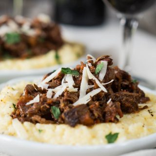 Side view of a white plate filled with cheesy polenta and topped with a mound of lamb Ragu garnished with parmesan cheese. A second plate sits in the background next to a glass of wine.