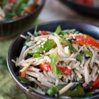 A black bowl filled with soba noodles with Asian flavors stuffed with red peppers and garnished with sesame seeds and cilantro. A second bowl sits in the background.