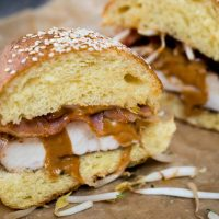 Two halves of a chicken sandwich layered with peanut sauce and bacon on a brioche bun.
