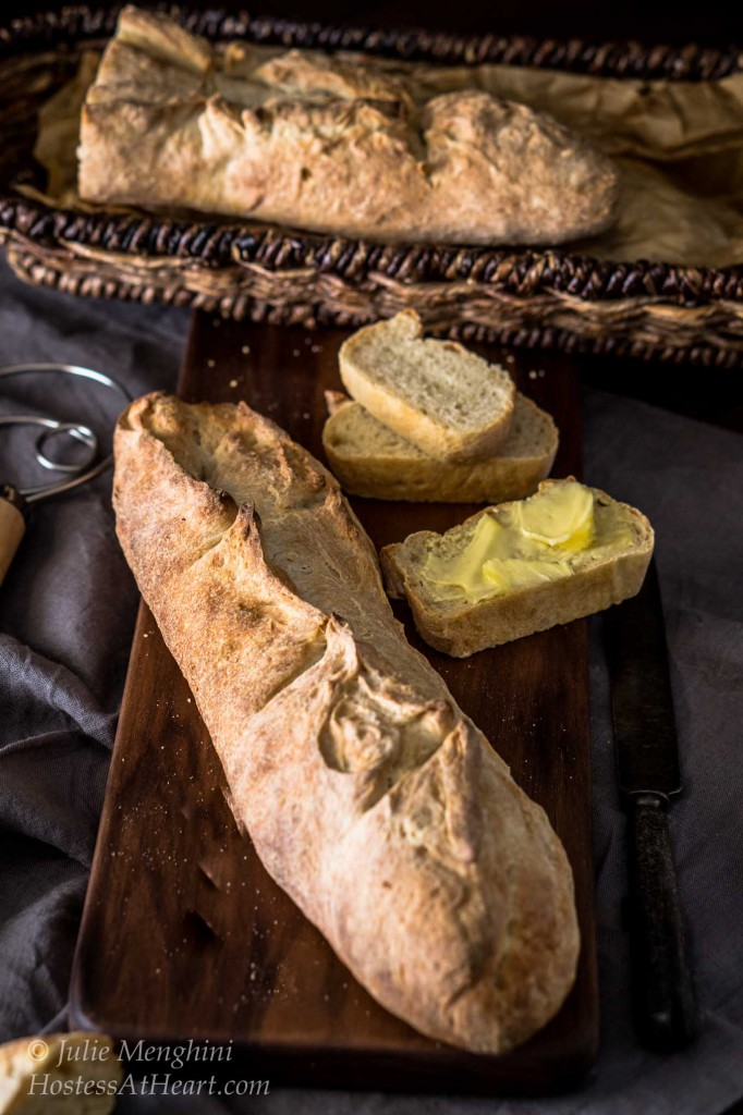 Top-down view of a loaf of a Garlic Batard sitting on a wooding cutting board next to cut slices slathered with butter. A blue napkin sits to the side and a basket of bread sits in the background.