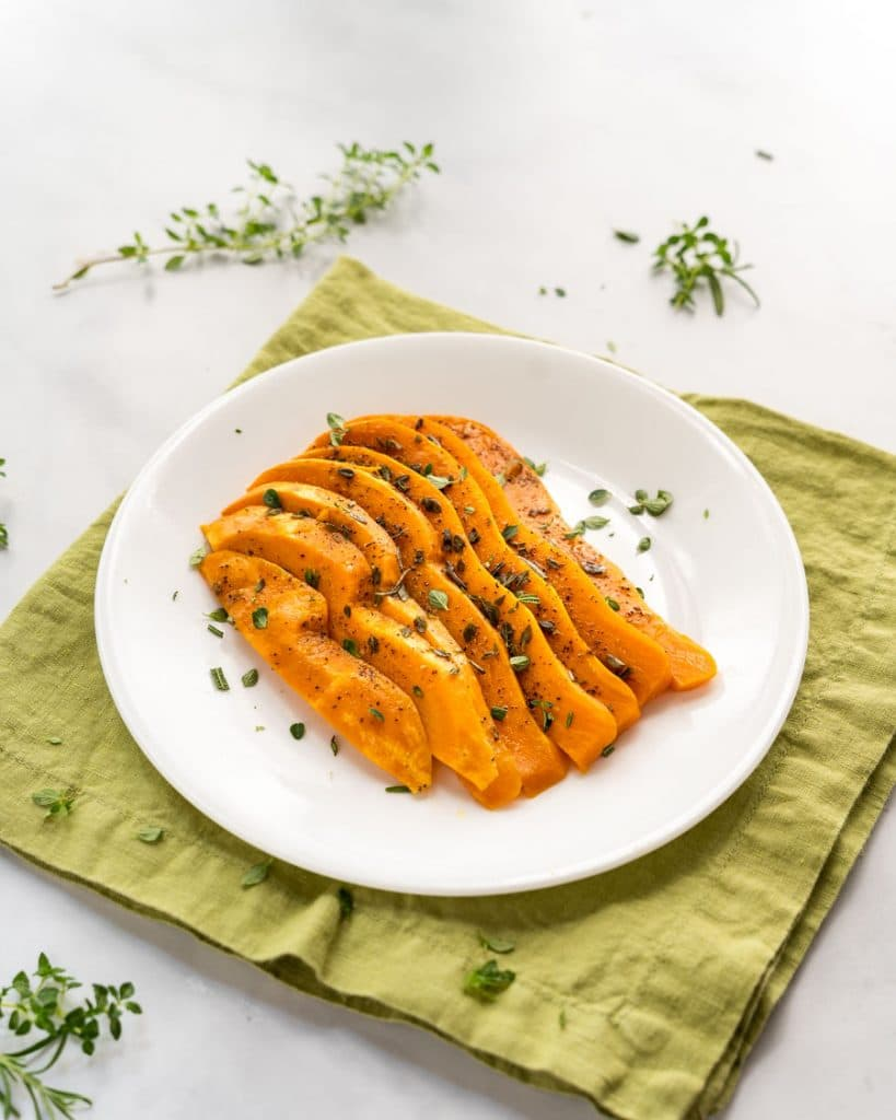 Cooked Sweet potato slices on a plate garnished with fresh herbs.