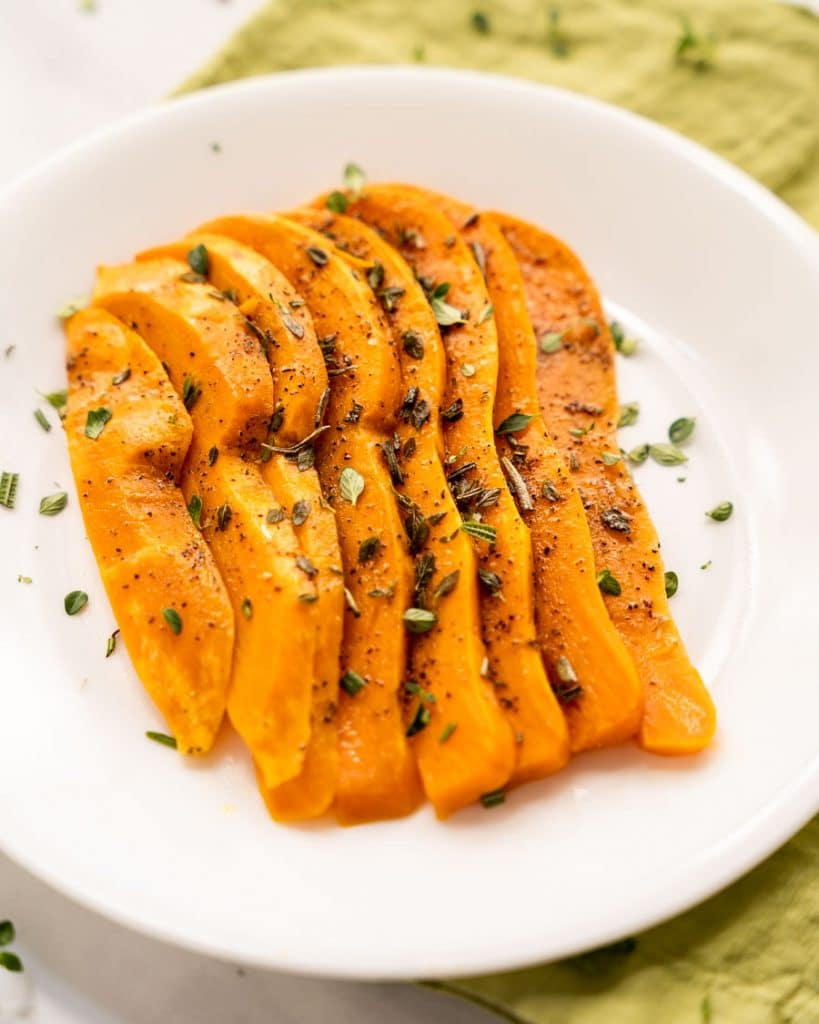 3/4 angle of sliced and fanned out sweet potatoes on a white plate.