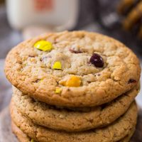 A stack of M&M cookies sitting on an antique butter paddle. A basket of cookies and a bottle of milk sit in the background.