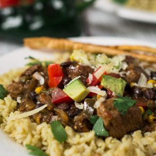 Poblano Pork Stew over Tomatillo Rice is rich in flavors and has a deliciously warm kick. It can be made in a crockpot or simmered on the stove. Either way, you're going to love this dish | HostessAtHeart.com