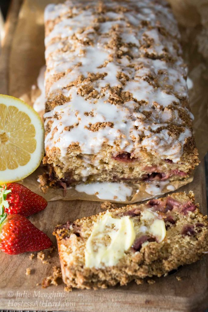 Top view of a loaf of Strawberry Rhubarb Bread with a streusel top that\'s drizzled with a glaze. The front piece has been cut from the loaf and is laying flat and covered in butter. Two strawberries and a slice of lemon sit to the side.