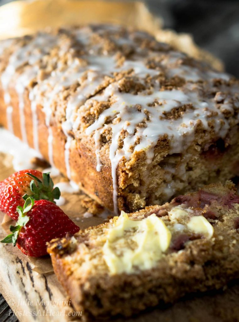 Side view of a loaf of Strawberry Rhubarb Bread with a streusel top that\'s drizzled with a glaze. The front piece has been cut from the loaf and is laying flat and covered in butter. Two strawberries sit to the side.
