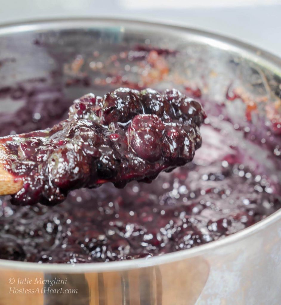 A wooden spoon filled with blueberry pineapple filling in a silver sauce pan.