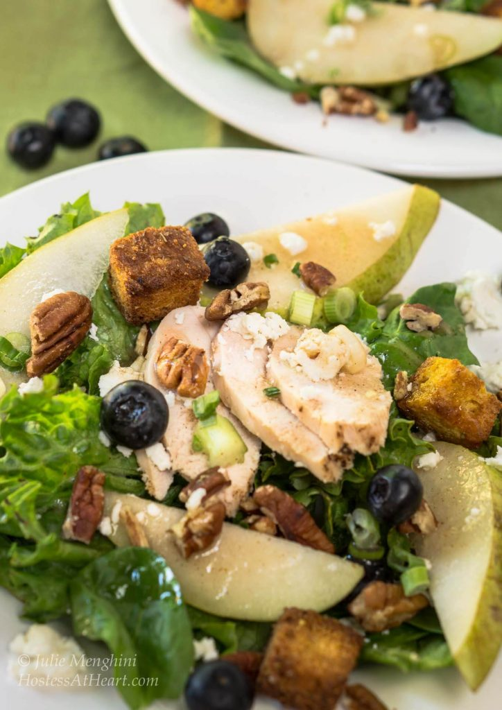 Green lettuce salad topped with sliced chicken, fresh pears, candied pecans, green onions, blueberries, and blue cheese crumbles. A second plate sits in the background.