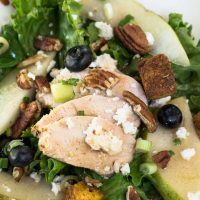 Green lettuce salad topped with sliced chicken, fresh pears, candied pecans, blueberries, and blue cheese crumbles.