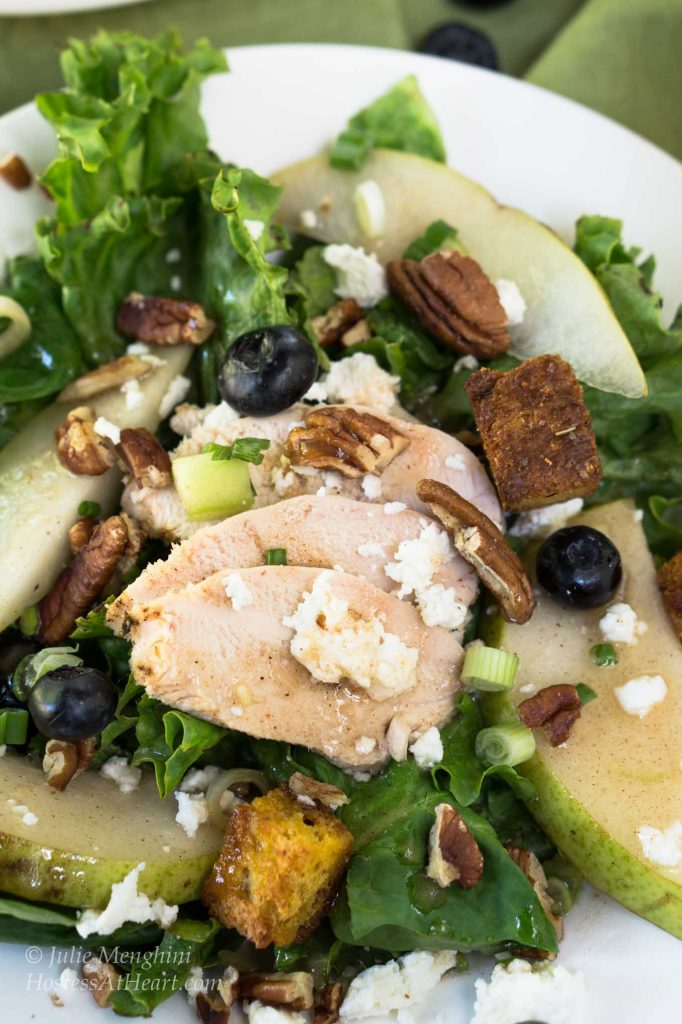 Green lettuce salad topped with sliced chicken, fresh pears, candied pecans, green onions, blueberries, and blue cheese crumbles.
