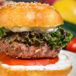 Close up of lamb burger between bun with tomato and sauce