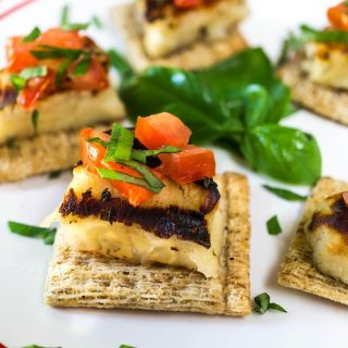 A white plate filled with several crackers topped with Grilled Halloumi cheese, diced tomato, and fresh sweet basil. Fresh sweet basil is in the center.