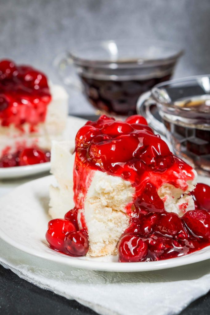 Angled photo of a piece of baked Meringue topped and spilling down the side with red cherries. A second piece and two cups of coffee sit in the background.
