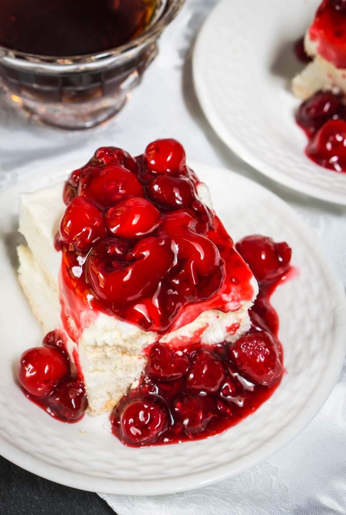 A piece of baked Meringue topped and spilling down the side with red cherries. Another plate and a coffee cup sit in the background.
