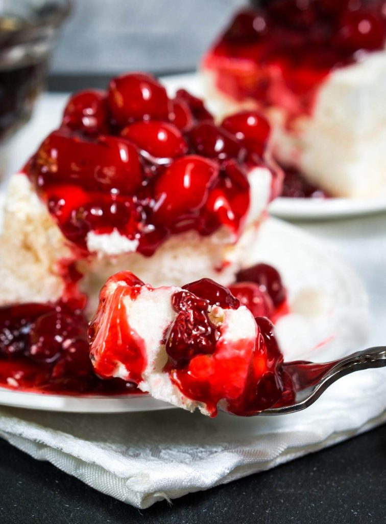 Table view of a piece of baked Meringue topped and spilling down the side with red cherries. A forkful of the dessert hovers in front of the dessert and a second piece appear in the background.