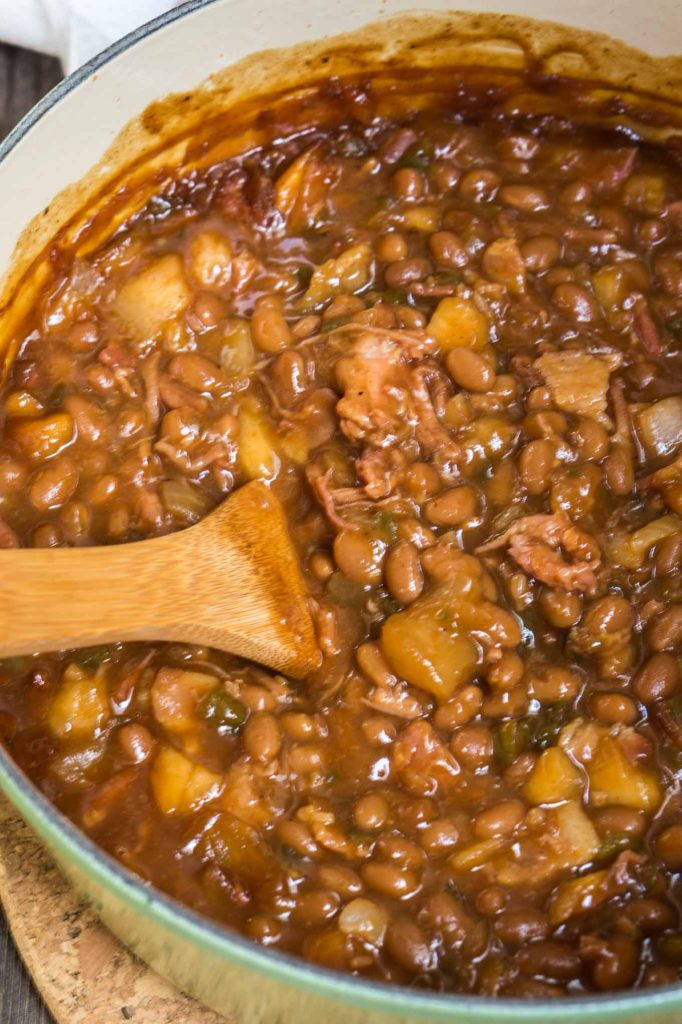 Looking down at a cast iron pot filled with baked beans, apples, shredded pork and jalapeno peppers with a wooden spoon on the side.