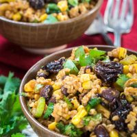 A brown bowl of a sweet and spicy Cherry Chipotle salad loaded with roasted corn, dried cherries, black beans, and garnished with cilantro. A second bowl sits in the background over a red napkin. A fork sits to the right of the back bowl and fresh cilantro to the left of the front bowl.
