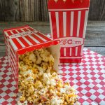 Popcorn box tipped over spilling Honey Nut Popcorn with bacon onto a red checked paper napkin. An upright box sits in the background,