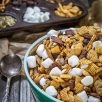 A green bowl filled with snack mix containing graham crackers shaped like bunnies, cereal squares, marshmallows, pretzel sticks, and chocolate chips. A muffin tin is in the back with the ingredients filling the muffin cavities.