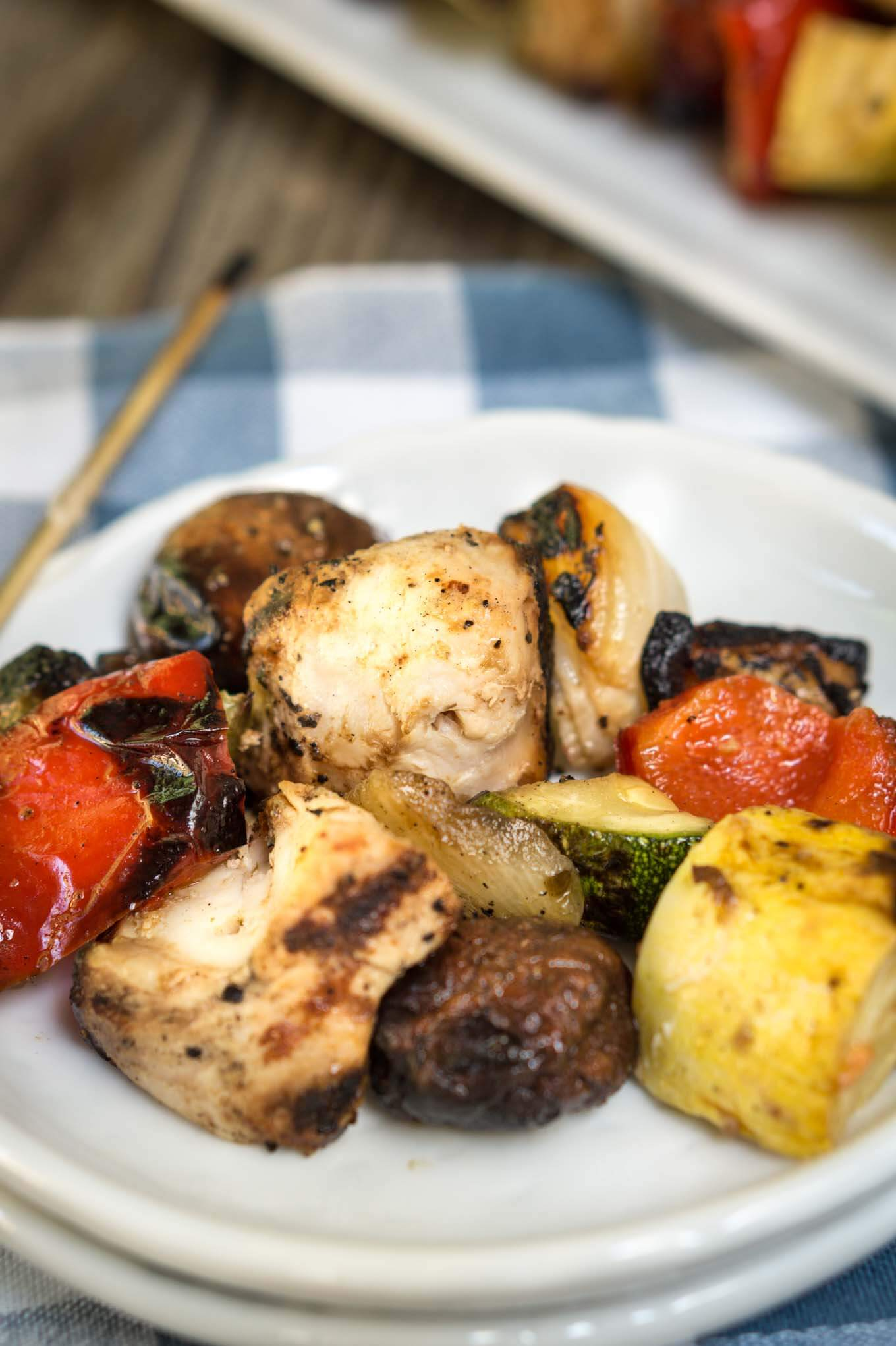 A plate of grilled Shish Kabobs filled with slices of squash, tomatoes, mushrooms, peppers, and chicken on a white plate over a blue checked tablecloth.