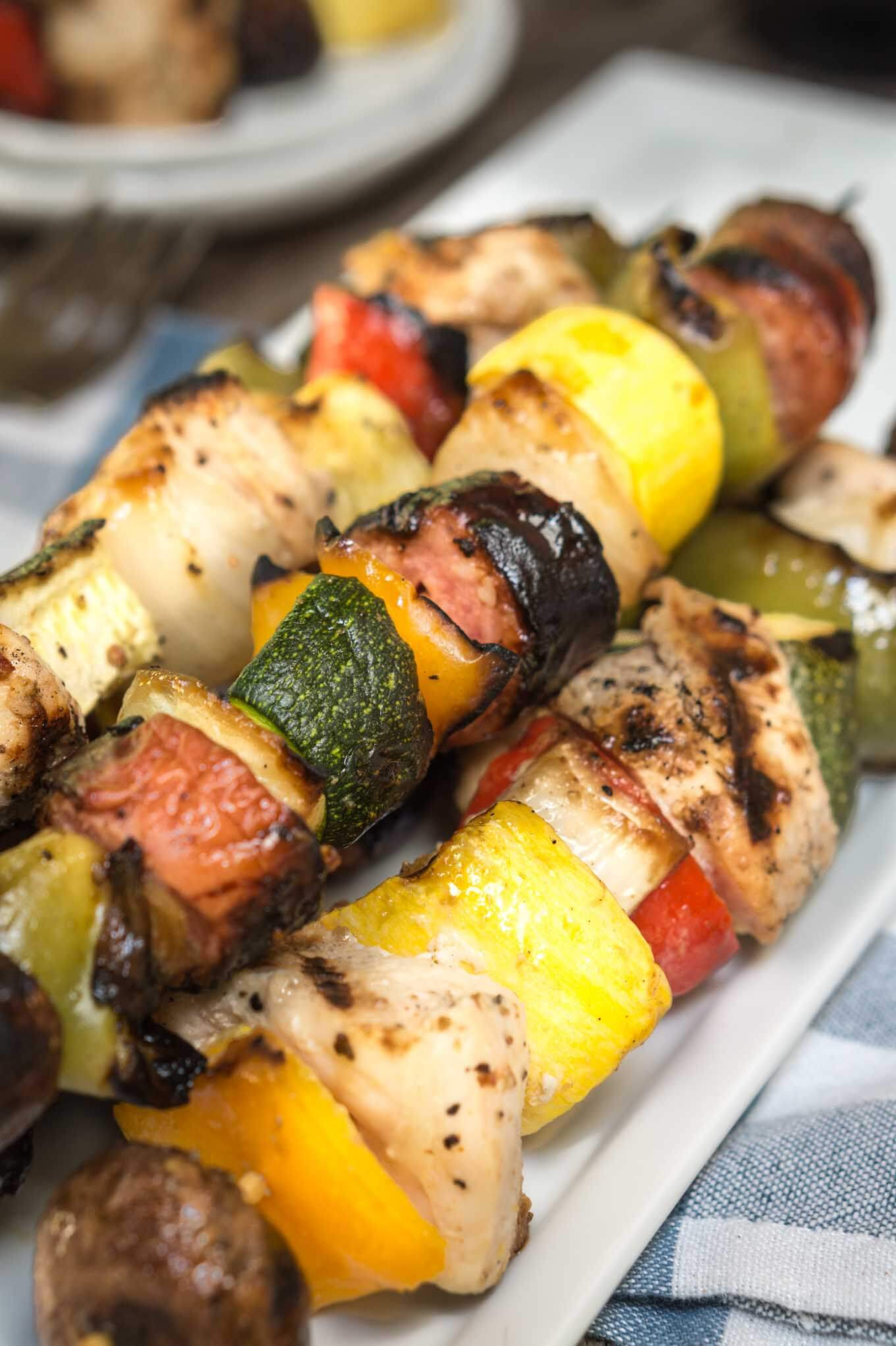 A pile of Shish Kabobs filled with slices of squash, tomatoes, mushrooms, peppers, and chicken on a white plate over a blue checked tablecloth. Empty plates sit in the background.