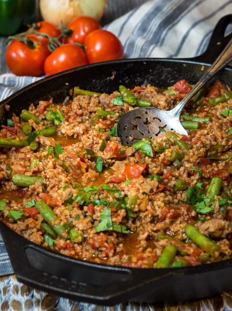 A cast-iron skillet full of a casserole filled with Sausage, Bulgur Wheat, Green Beans, and Tomatoes and then garnished with fresh parsley. A large spoon is in the pan. Fresh tomatoes sit in the background over a striped napkin.