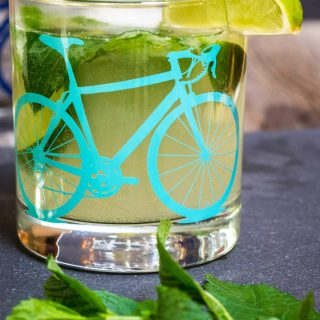 A front view of a slate tray topped with a Mojito topped with fresh mint in a glass with a bicycle on the front. A slice of lime garnishes the glass. Fresh mint sits in the foreground.