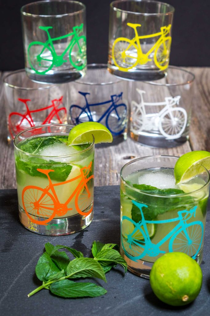 Several glasses with different colored bicycles on the front sitting on a wooden board. Some are filled with mojitos garnished with mint and slices of lime.