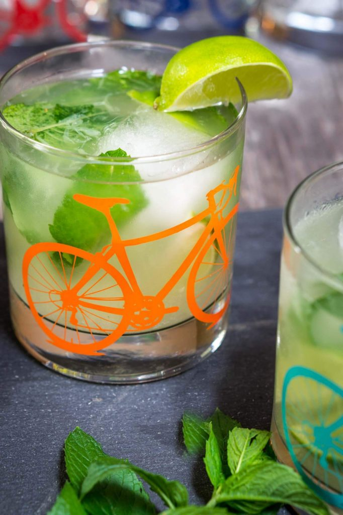 A front view of a slate tray topped with a Mojito topped with fresh mint in a glass with a bicycle on the front. A slice of lime garnishes the glass. A partial glass sits to the right front.