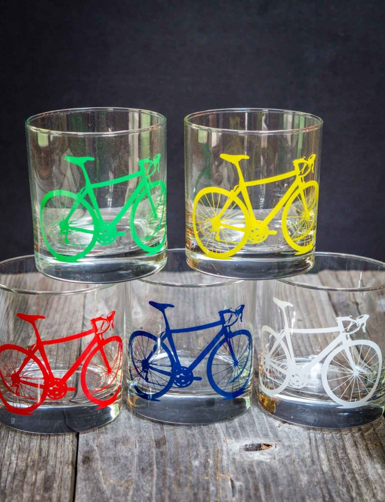 5 glasses with different colored bicycles on the front sitting on a wooden board.
