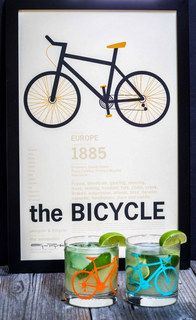 "A front view of two Mojitos topped with fresh mint in a glass with a bicycle on the front. A slice of lime garnishes the glass. The glasses sit in front of a print titled ""The Bicycle\""."