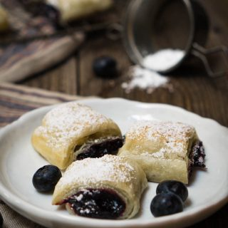The blueberry puff pastry rolls on a white plate with the title of the recipe printed on top of the photo
