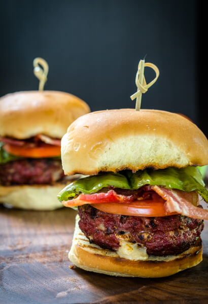 Side view of a hamburger that\'s been stuffed with Pepperjack cheese and pepperoncini sitting over a slice of tomato and lettuce between a bun. A skewer secures the bun to the burger. A second burger sits in the background.