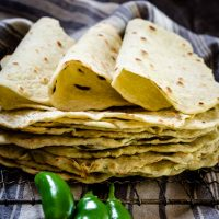 A stack of homemade tortilla shells on a cooling rack with three folded tortillas on top. 3 fresh jalapenos sit in the front and a blue striped towel sits in the background.
