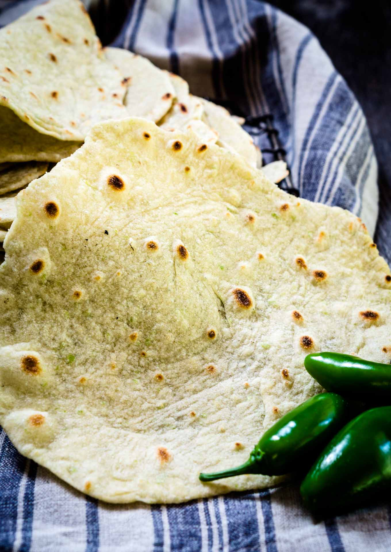 A close up of a fresh tortilla with fresh jalapenos sitting in the foreground.