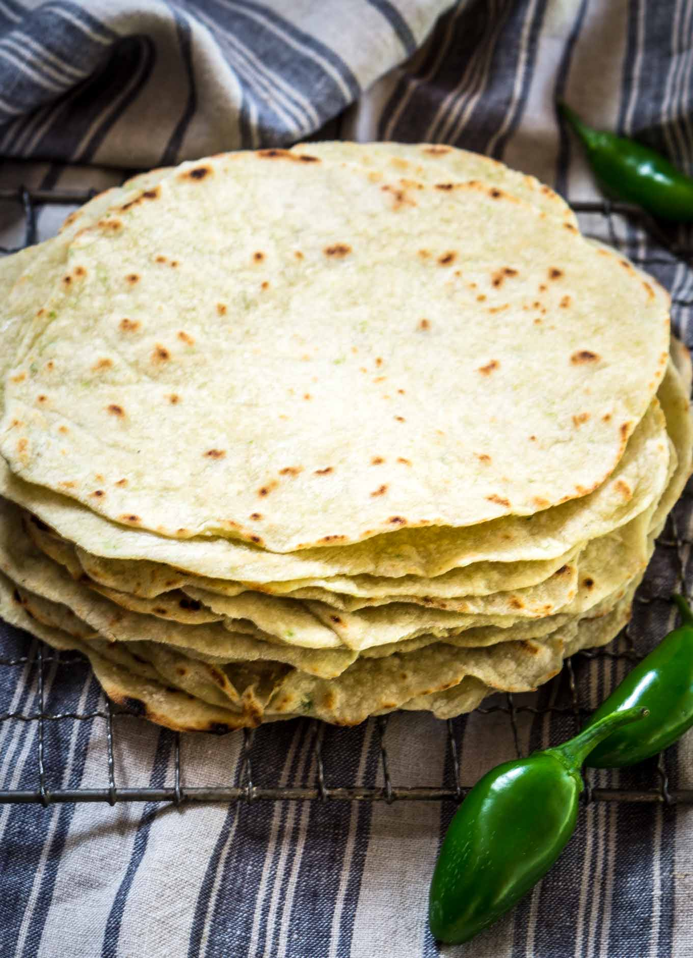 A stack of homemade tortilla shells on a cooling rack. Fresh jalapenos sit in the front and back.