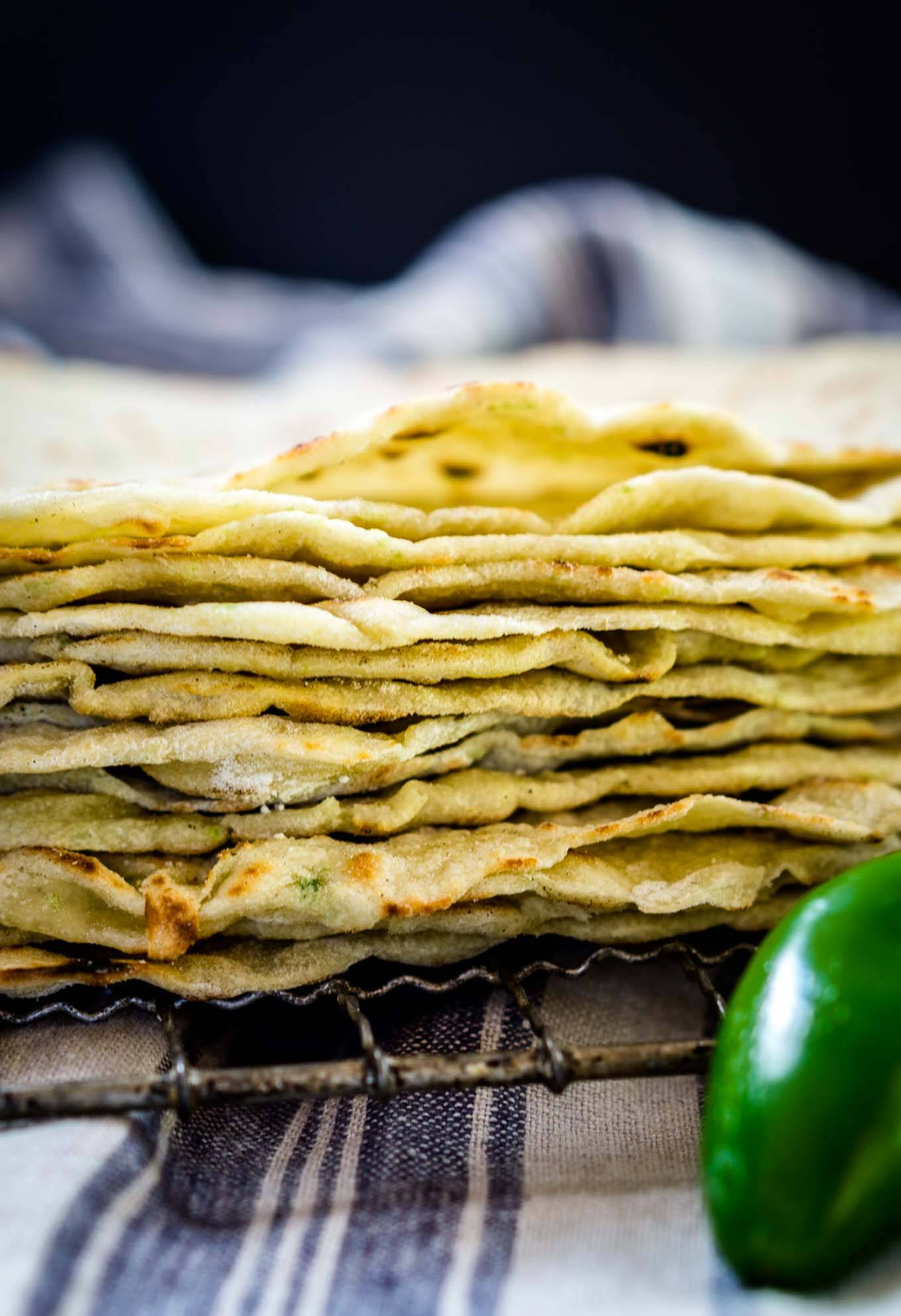 A stack of homemade tortilla shells on a cooling rack. A fresh jalapeno sits in the front and a blue striped towel sits in the background.