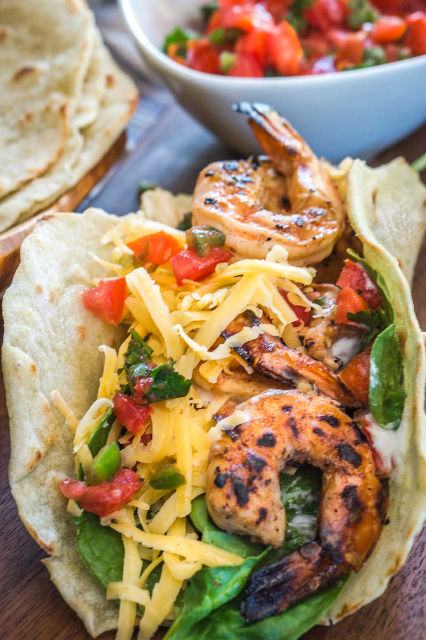 Sideview of a taco shell filled with lettuce, diced tomatoes, and cheese, topped with Raspberry jalapeno Shrimp. A bowl of fresh pico and a jalapeno sit in the background.