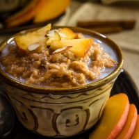 A yellow dish filled with Steel-cut Oats and Bulgar that's topped with warm milk, cinnamon, fresh peaches, and nuts. Fresh sliced peaches sit to the side.