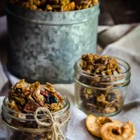 Two small jars of granola sit in small jars with a larger tin of granola in the background. Dried apples sit in the foreground.
