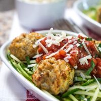 A white bowl of spiralized zucchini topped with chicken meatballs and marinara.