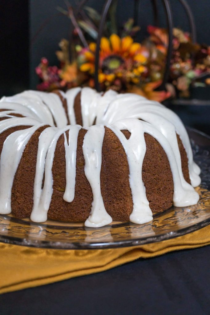 Bundt cake with icing drizzled over the top and dripping onto the serving platter with fall flowers sitting behind it.