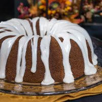 Pumpkin Bundt cake with icing drizzled over the top and dripping onto the serving platter with fall flowers sitting behind it.