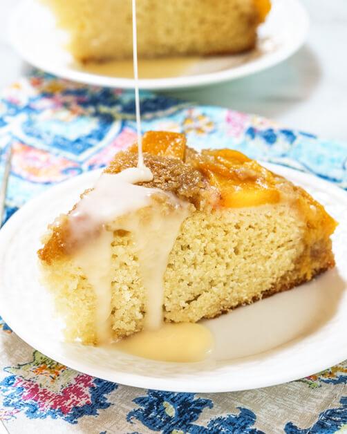 A slice of Upside-Down Peach Cake with a pour of Hot Rum Sauce and peaches running over the top
