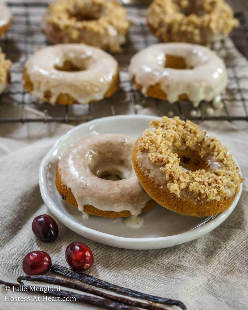 Two baked donuts on a white plate. The front forward one is topped with glaze and rolled in nuts. The back one is glazed. A cooling rack holding more donuts sit in the background.