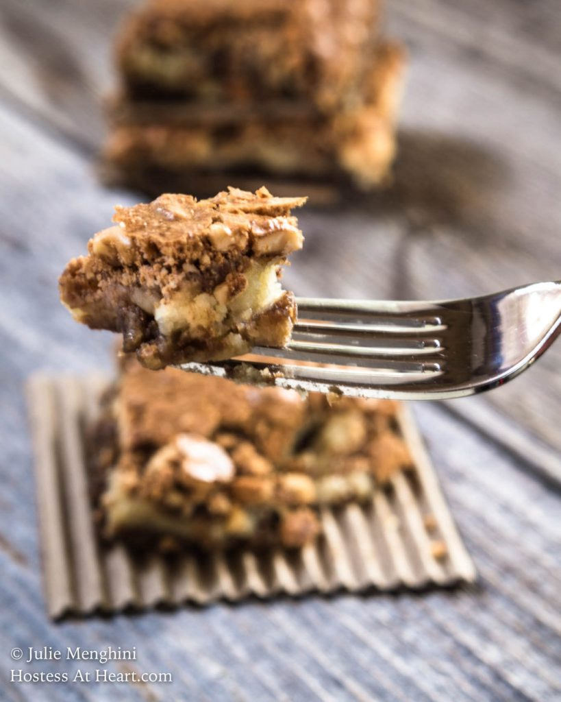 A forkful of a hazelnut cookie bar hovering over a hazelnut cookie bar sitting on a piece or corrugated cardboard.