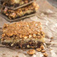 A top angle view of a Hazelnut Cookie Bar sitting on a piece of parchment paper. Fresh chopped hazelnuts sit in the foreground. Additional bars are stacked in the background.