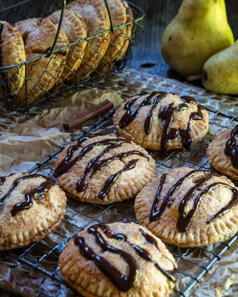 A cooling rack over a wooden matt filled with Pear Hand Pies drizzled with dark chocolate. Two raw pears and a wire basket of pies sit in the background.