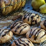 Round-shaped pear hand pies that have been drizzled with dark chocolate over a cooling rack. A basket of additional pies sits in the back next to fresh pears.