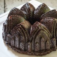 A top-angled view of a raspberry glazed chocolate raspberry bundt pan sitting on a white plate.